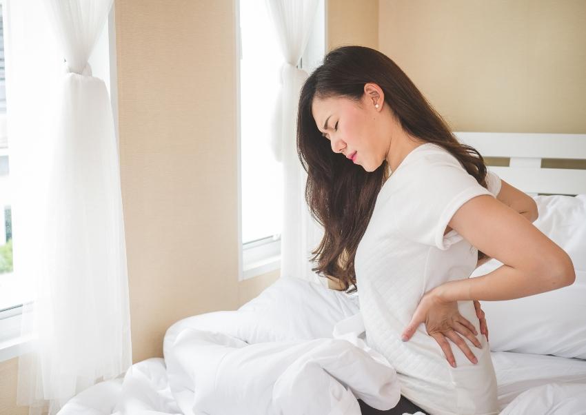 Junge Frau mit Rückenschmerzen, sitzend auf einem Bett