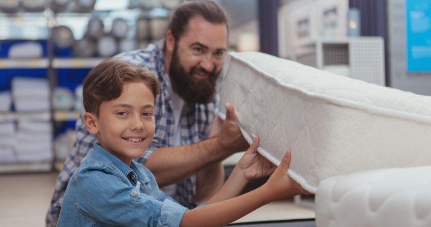 Vater und Sohn beim Matratzenneukauf -Neue Matratze: Eingewöhnungszeit und körperliche Umstellung
