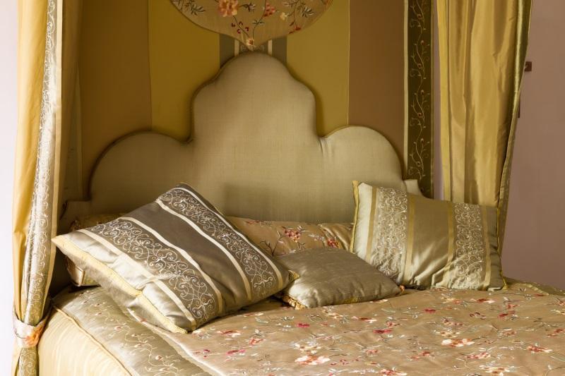 Das Kopfende eines prachtvollen Paradebetts. Große, goldfarbene Kissen und die aufwendig bestickte Bettwäsche wirken sehr beeindruckend. Die Geschichte des Bettes
