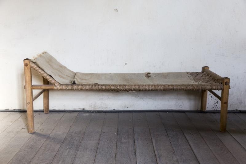 Eine antike Holzliege - der Lattenrost ist aus Holzfasern geflochten. Die Geschichte des Bettes