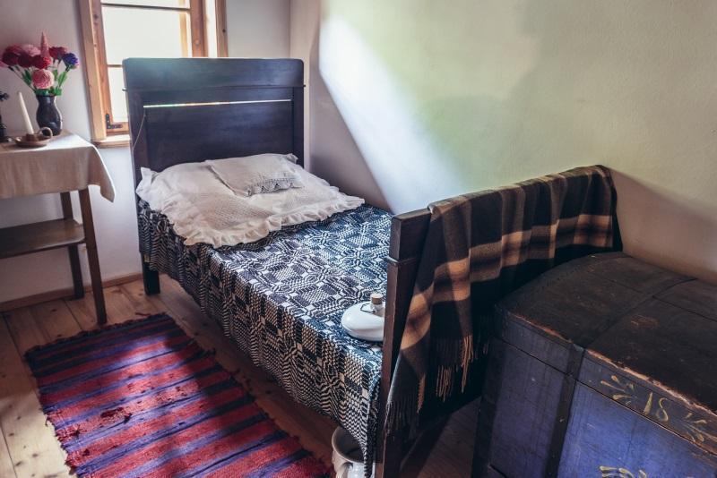 Ein altes, hözernes und kurzes Bett. Unter dem Bett steht der Nachttopf, am Fußende befindet sich eine schwere alte Holztruhe Die Geschichte des Bettes