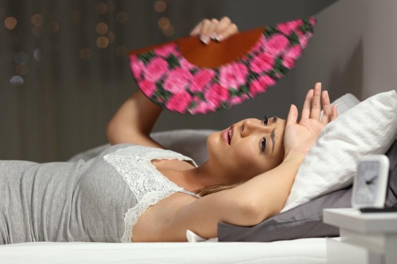 Eine Frau liegt schwitzend im bett und fächert sich Luft zu Schlafzimmertemperatur und Luftfeuchte