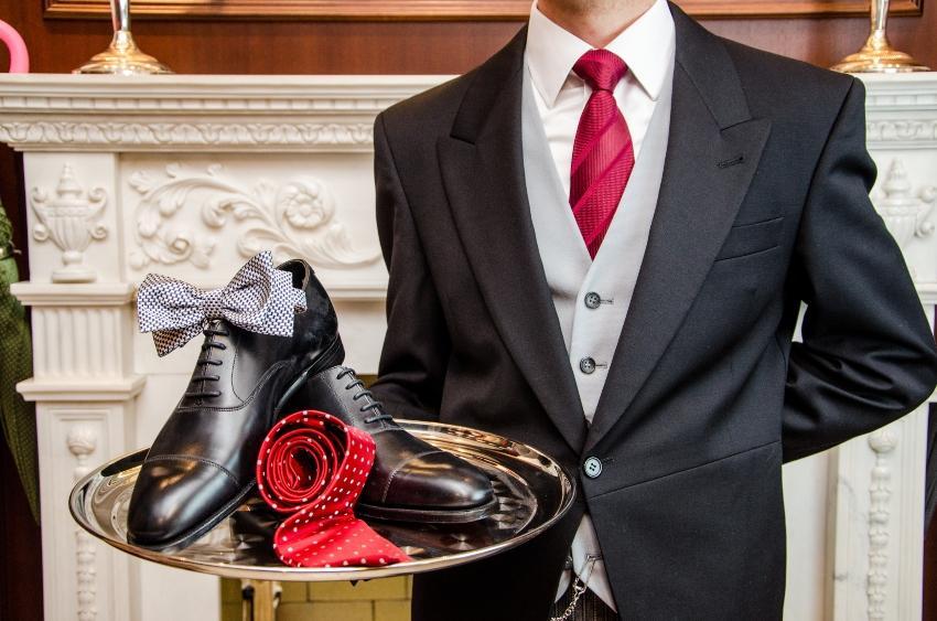 Diener trägt Tablett mit Schuhen und Krawatte darauf