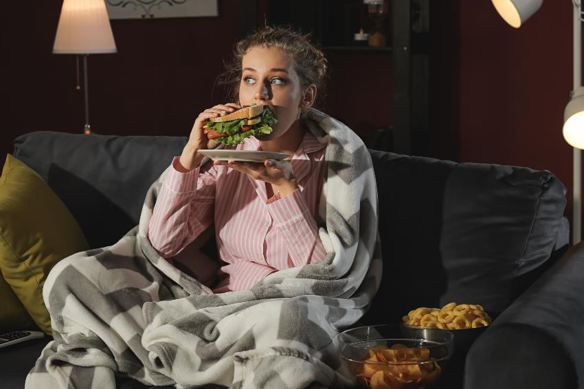 Junge Frau sitzt auf Couch und isst Sandwich - Heißhunger als mögliches Symptom beim Kleine-Levin-Syndrom