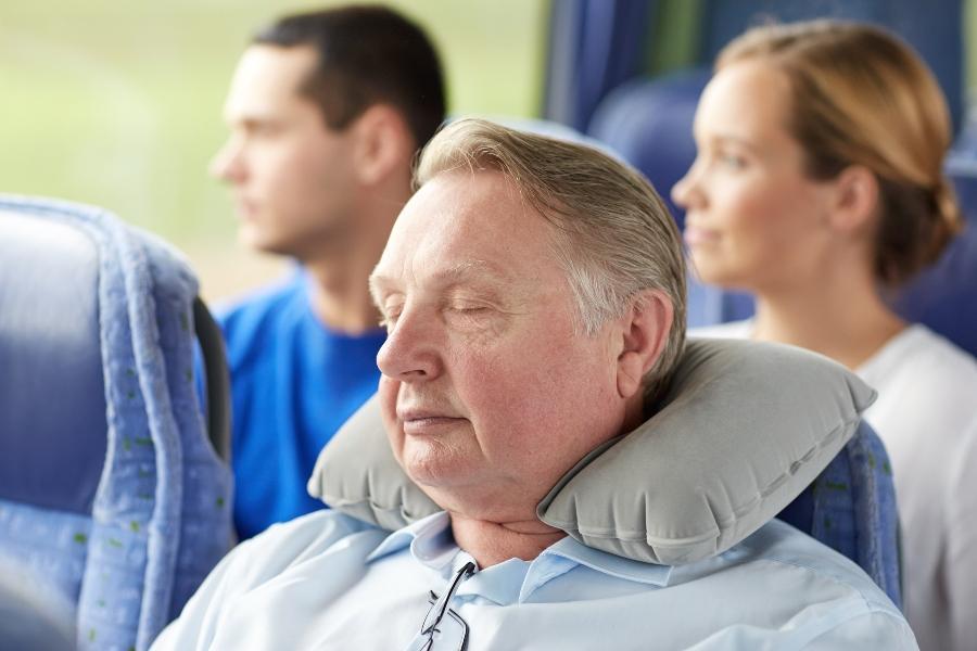 Aelterer Mann schlaeft mit Nackenkissen schlafen-im-zug