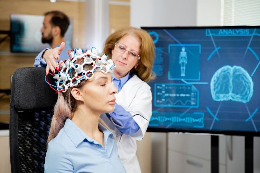 Junge Frau bei moderner Hirnstrommessung bei einer Fachärztin