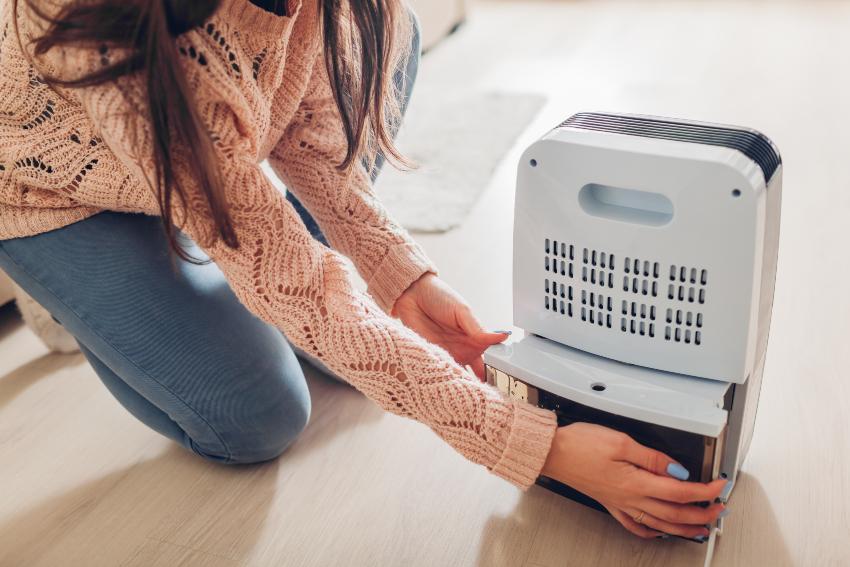 Frau bedient elektrischen Luftentfeuchter - die optimale Temperatur im Schlafzimmer sollte vorhanden sein
