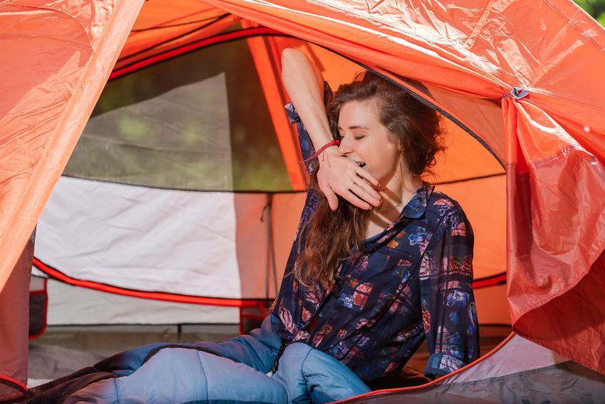 Frau gähnt im Zelt - bequem schlafen im Zelt bedarf einiger Vorbereitung