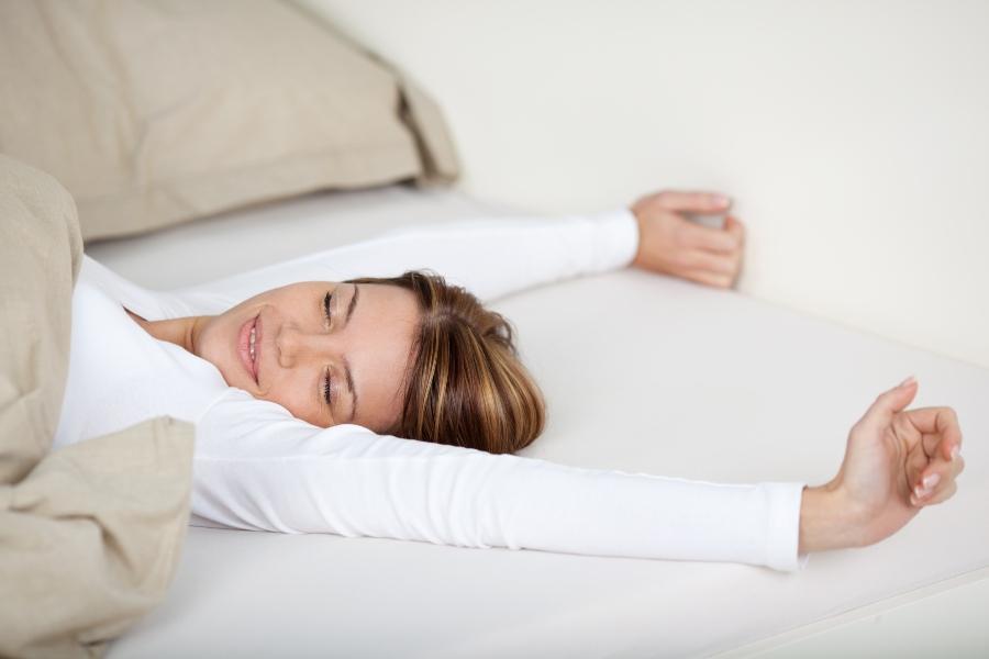 laechelnde frau streckt sich im bett matratzen-mit-coolmax-bezug