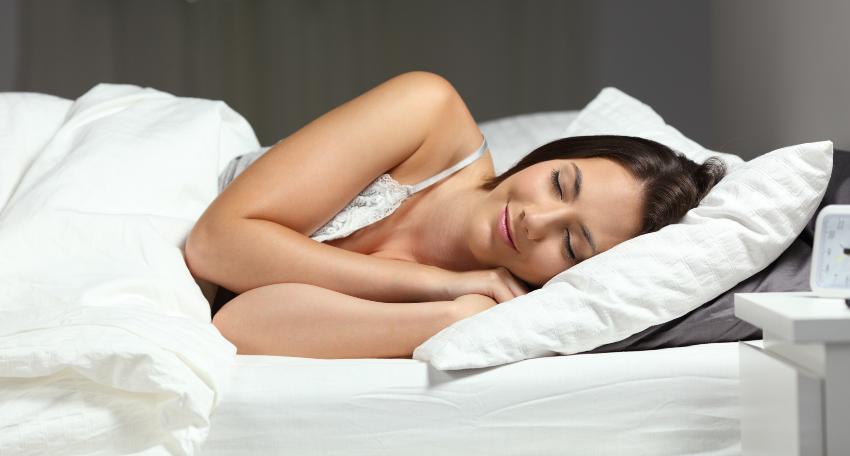 Junge Frau in Seitenschläferposition - die richtige Bettgröße ist entscheidend