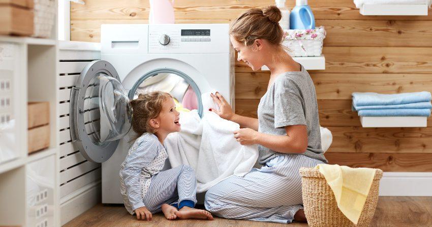 Textilpflege für das Bett - Mutter und Tochter vor der Waschmaschine