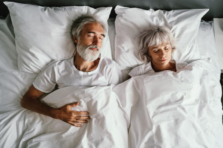 Ein älteres Paar schläft firedlich nebeinander im Bett - Betten im Vergleich