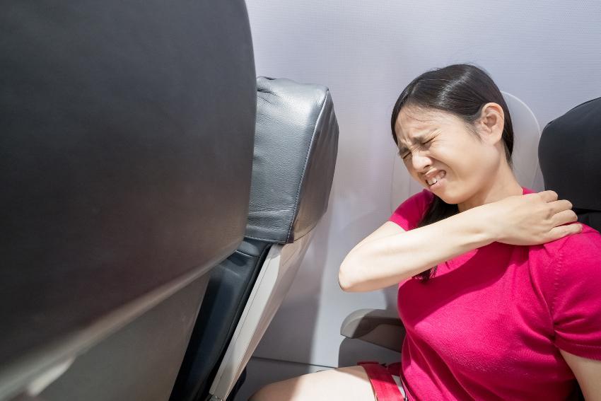Frau hat Rückenschmerzen im Flugzeug