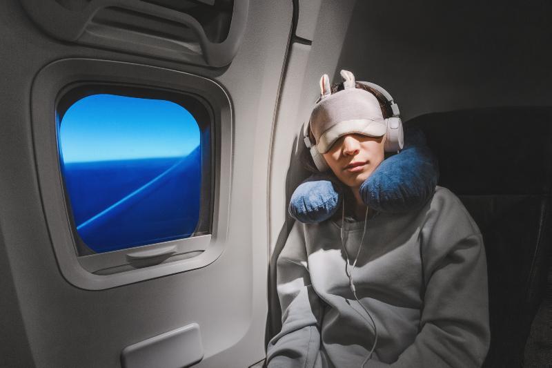 Frau schläft im Flugzeug mit Nackenhörnchen, Kopfhörern, und Schlafmaske