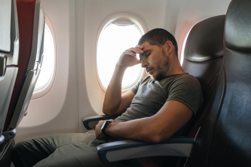 Mann hat Schwierigkeiten, im Flugzeug zu schlafen
