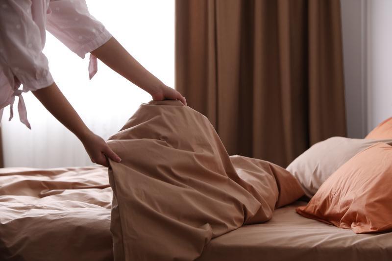 Eine Frau schüttelt die Bettdecke auf, um die Füllung gleichmäßig zu verteilen. Dieses Problem besteht bei Steppdecken nicht