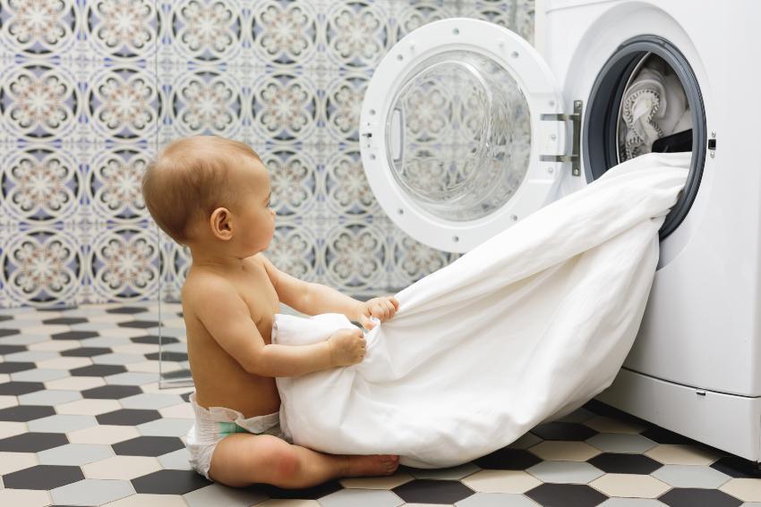 Baby sitzt vor Waschmaschine mit Bettdecke