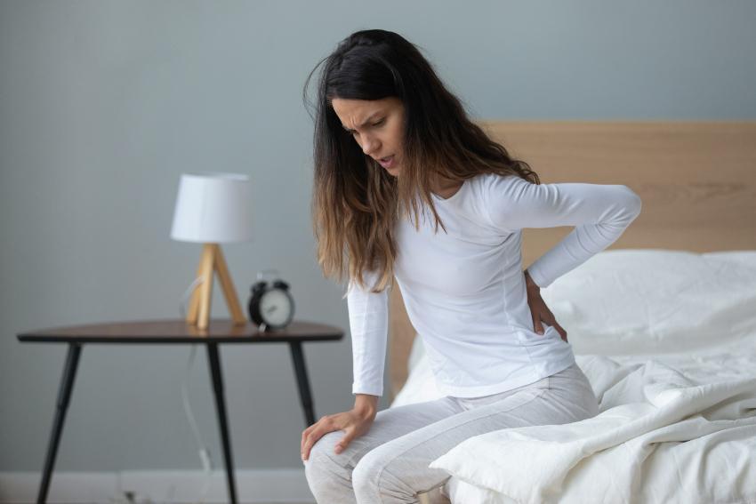 Frau steht auf, mit Rückenschmerzen