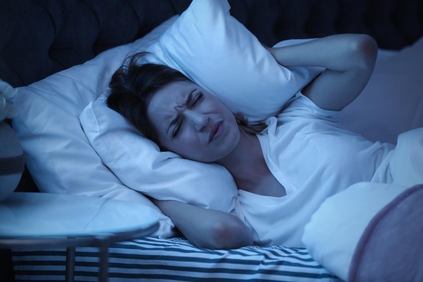 Frau hält sich Kissen vor die Ohren - wenn das Bett quietscht ist erholsamer Schlaf unmöglich
