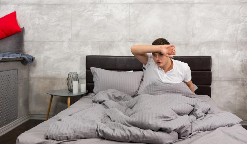 Mann sitzt schwitzend im Bett