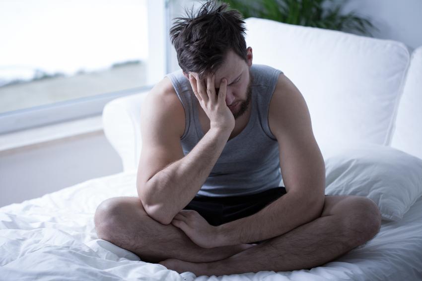 Mann sitzt unausgeschlafen im Bett