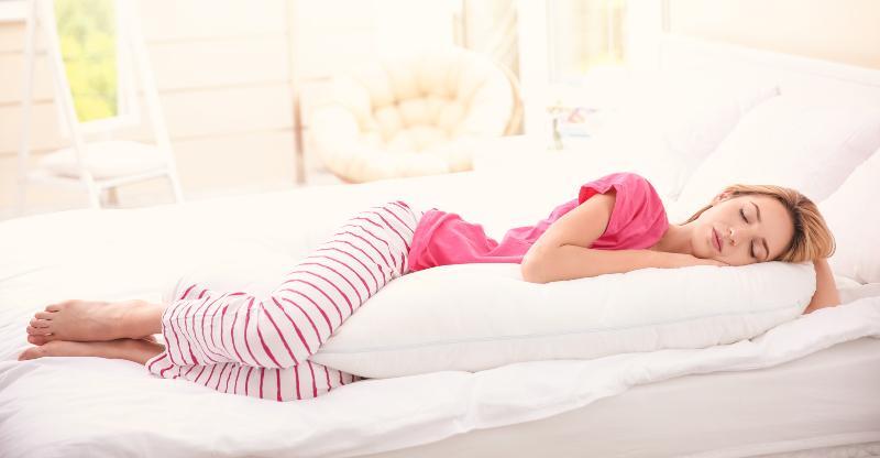 Eine junge Frau liegt in Seitenschläferposition im Bett und schläft