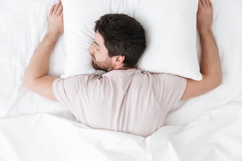 Mann schläft in Bauchlage