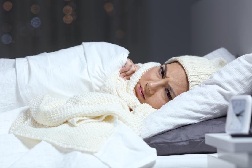 Frau mit Winteraccessoires im Bett