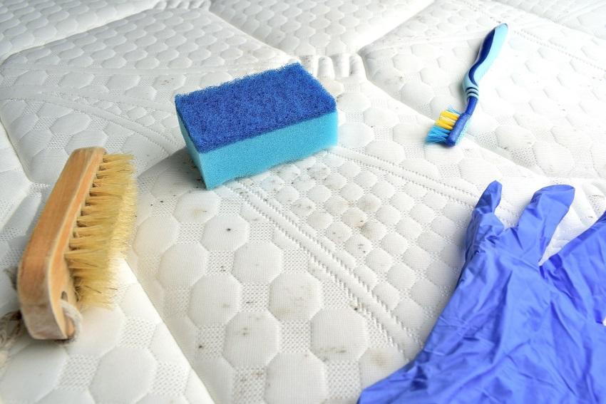 Schwamm, Bürste, Putzhandschuh und eine Zahnbürste liegen auf einer verschmutzten Matratze