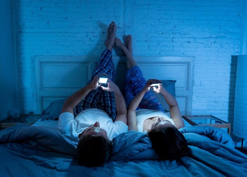 Paar im Bett mit Smartphones