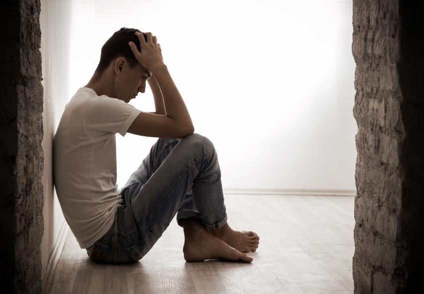 Junger Mann sitzt auf dem Boden, den Kopf in die Hände gestützt