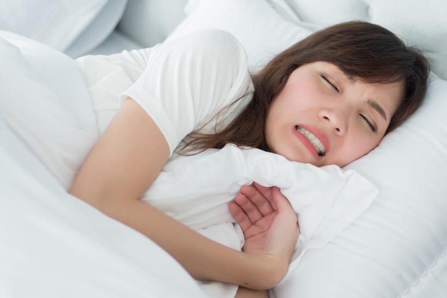 Frau knirscht im Schlaf mit ihren Zähnen