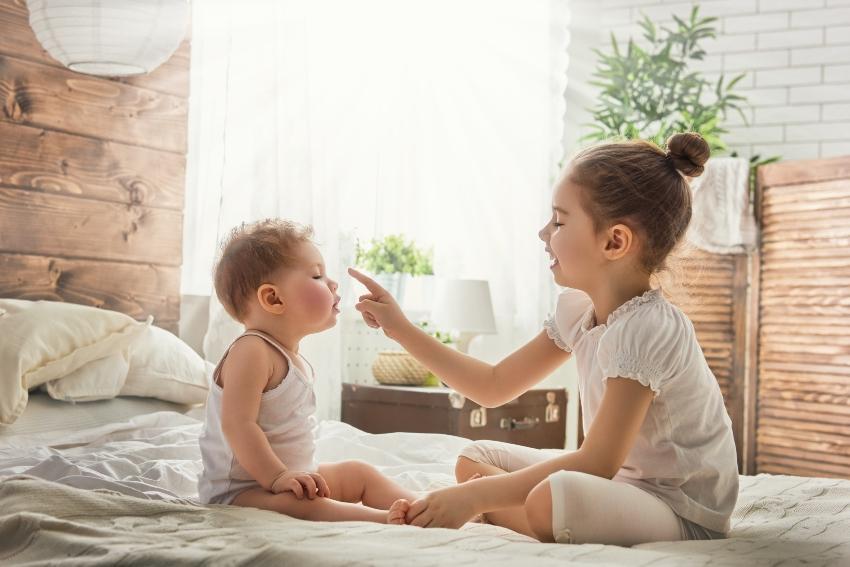 Kleine Geschwister spielen im Elternbett