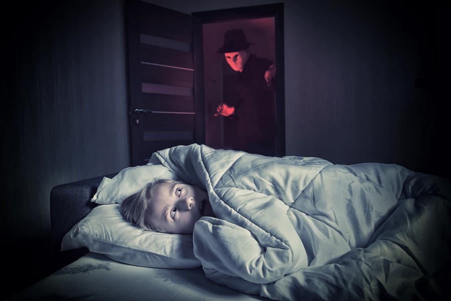 Junge liegt im Bett und hat einen Alptraum - Parasomnie