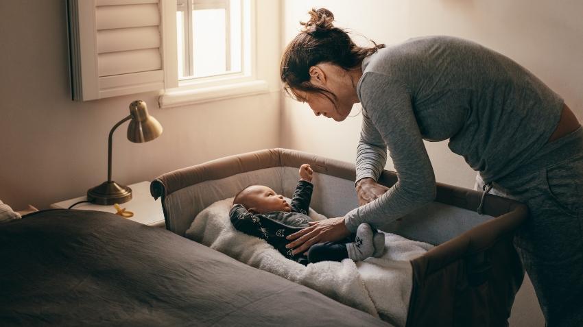 Mutter kümmert sich um Baby im Bett neben dem Elternbett - Babybett im Elternschlafzimmer
