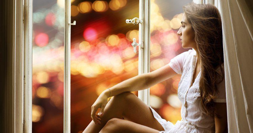 Schlaflose Frau mit Stadtlichtern im Hintergrund