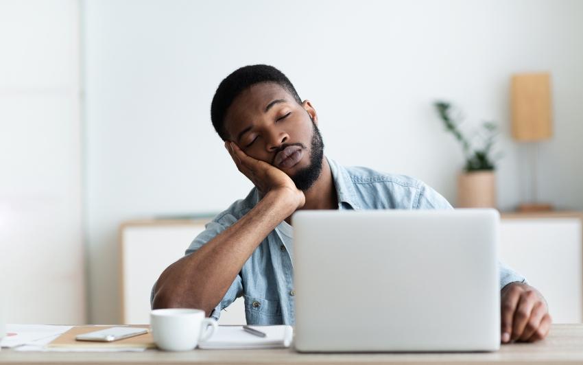 Mann schlafend am Laptop