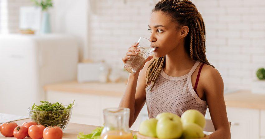 Frau trinkt ein Glas Wasser am Morgen