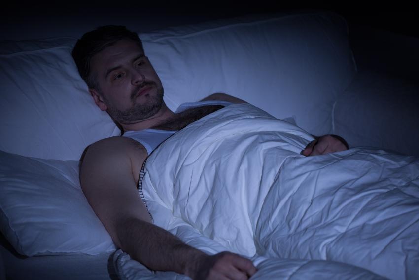Mann liegt im Bett und kann nicht schlafen