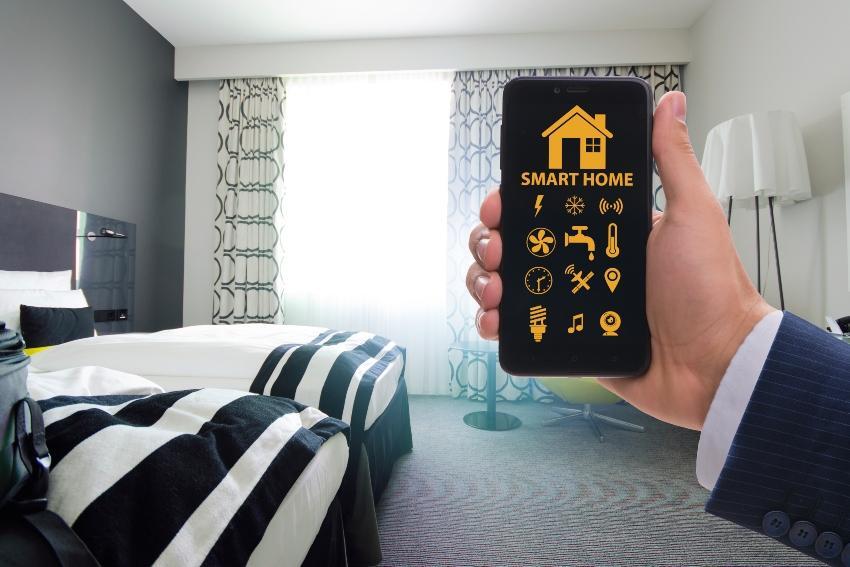 Mann mit Handy Apps kontrolliert sein Schlafzimmer - Schlafzimmer lüftenist wichtig