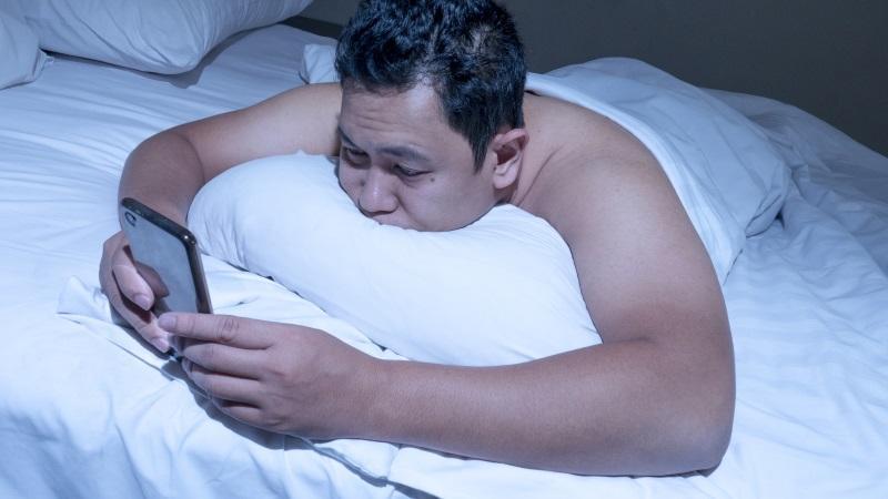 Ein Mann lieg im Bett und starrt auf sein Smartphone. Der gestiegene medienkonsum kann eine Ursache von regelmäßigen Schlafstörungen sein