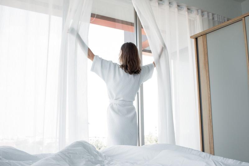 Eine Frau lüftet das Schlafzimmer, viel frische Luft hilft, um die Silberfische los zu werden.