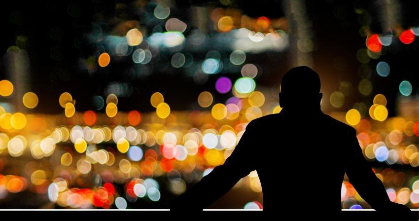 Mann auf dem Balkon mit Stadtlichtern im Hintergrund
