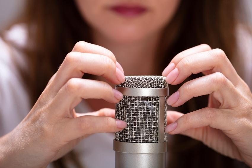 Frau kratzt mit Fingern auf einem Mikrofon (ASMR)