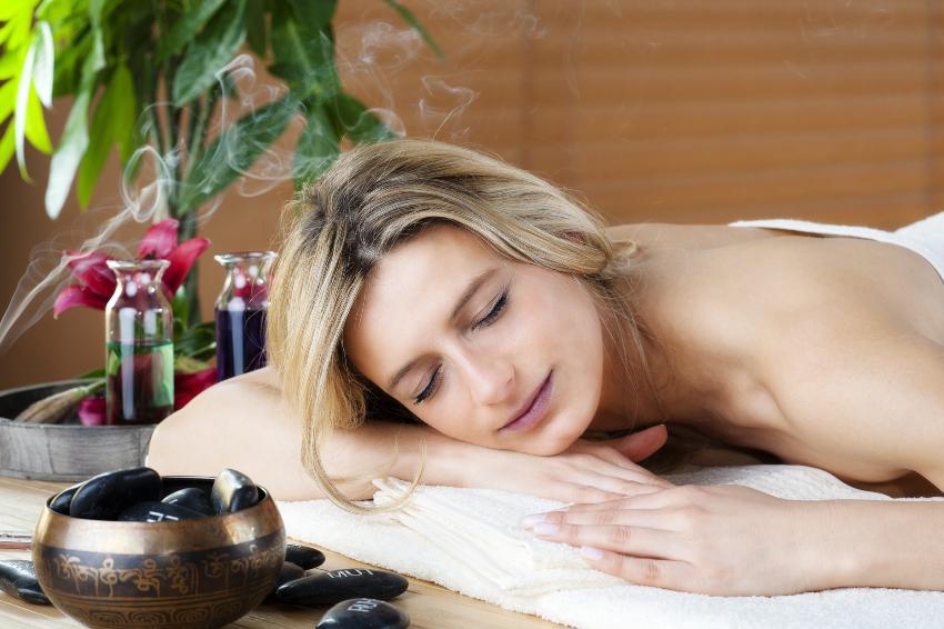 Frau liegt auf Decke neben Räucherkerzen und diversen Ölen