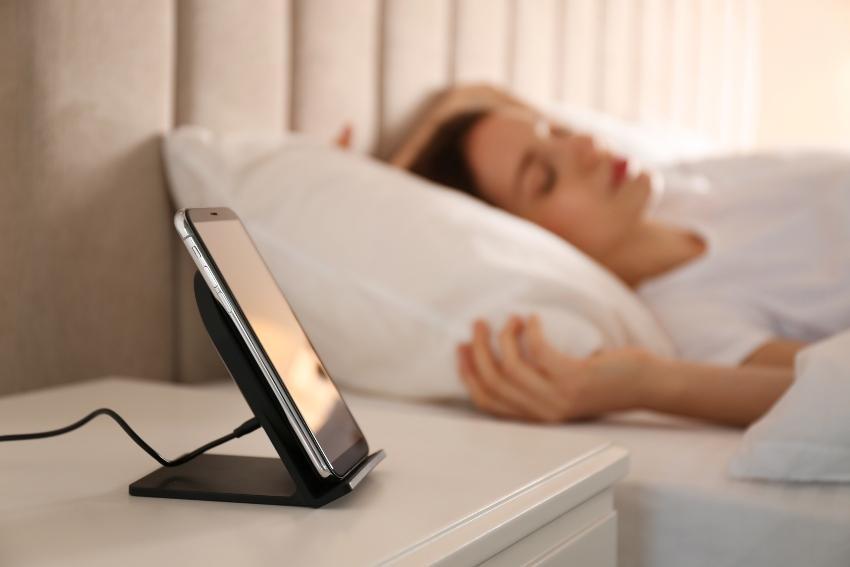 Junge Frau schläft im Bett; Handy steht auf dem Nachttisch - Mit Musik einschlafen