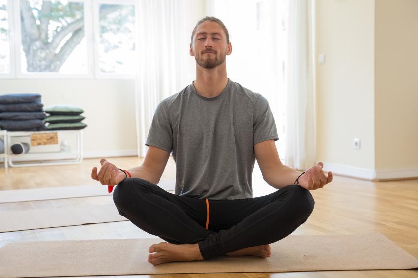 Mann macht Yoga auf Yogamatte - Entspannungsübungen vor dem Schlafen