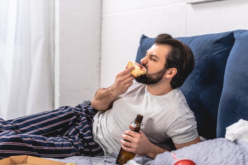 Mann liegt im Bett mit Sandwich und Bier