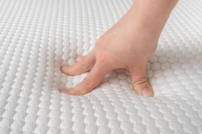 Ein Hand prüft die Elastizität einer Matratze, indem sie kräftig auf Oberfläche drückt Punktelastizität bei Matratzen
