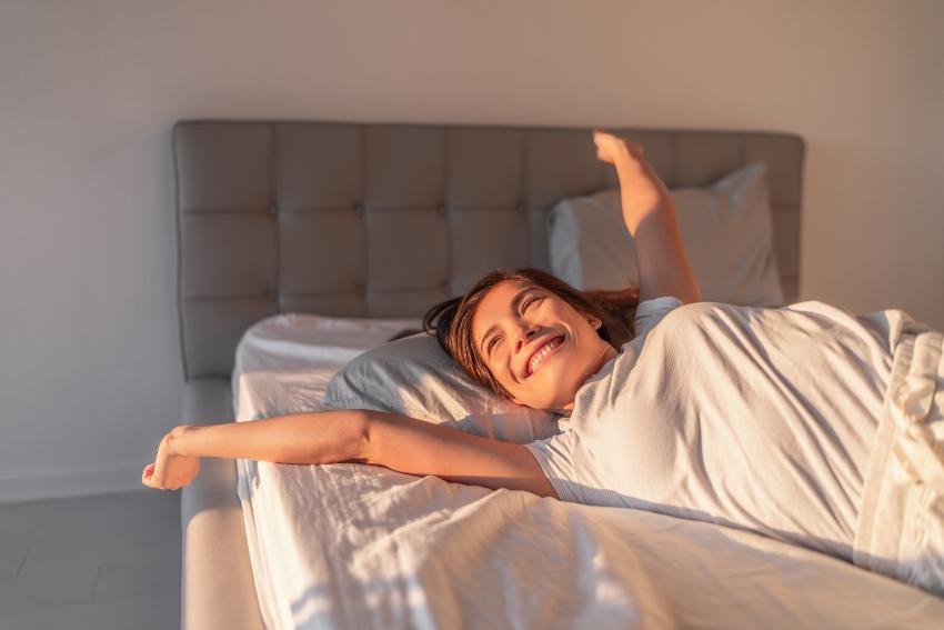 Junge Frau wacht glücklich auf - Was passiert im Schlaf mit Körper und Gehirn?